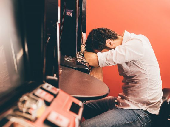 Image of man at a pokie machine